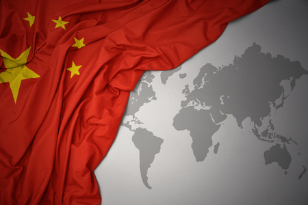 waving colorful national flag of china on a gray world map background.