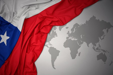 waving colorful national flag of chile on a gray world map background.