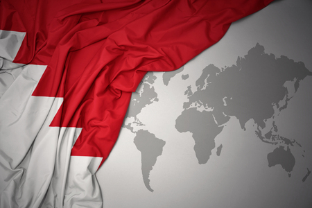 waving colorful national flag of bahrain on a gray world map background.