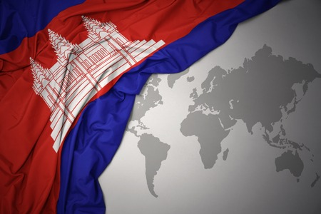 waving colorful national flag of cambodia on a gray world map background.