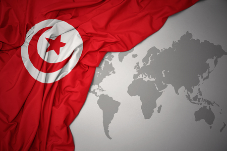 waving colorful national flag of tunisia on a gray world map background.
