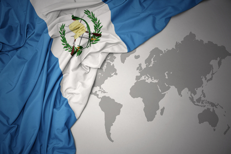 waving colorful national flag of guatemala on a gray world map background.