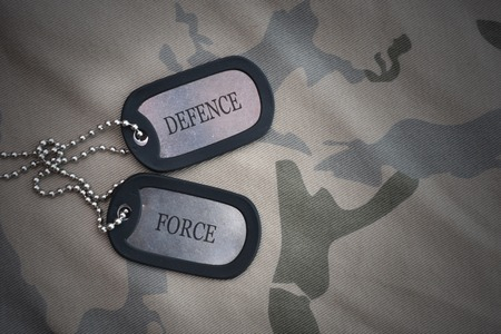 army blank, dog tag with text defence force on the khaki texture background. military concept