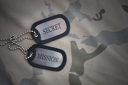army blank, dog tag with text secret mission on the khaki texture background. military concept