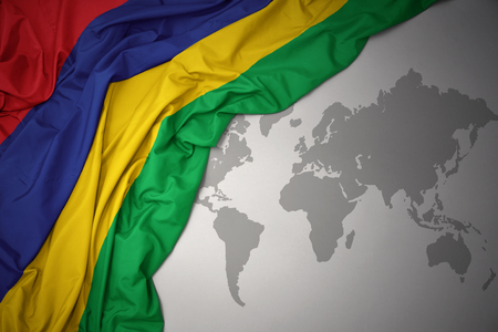 waving colorful national flag of mauritius on a gray world map background.