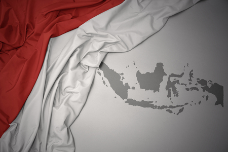 waving colorful national flag of indonesia on a gray map background.
