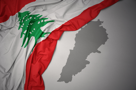 waving colorful national flag of lebanon on a gray map background.