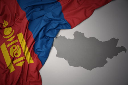 waving colorful national flag of mongolia on a gray map background.