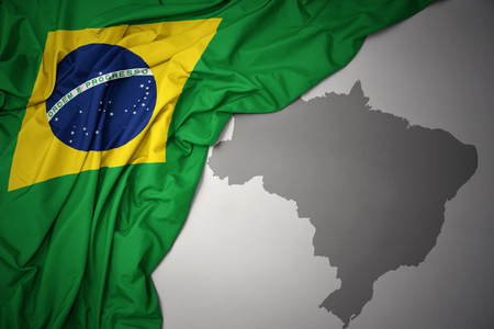 waving colorful national flag of brazil on a gray map background. Фото со стока