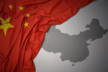waving colorful national flag of china on a gray map background.
