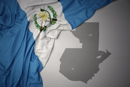 waving colorful national flag of guatemala on a gray map background.