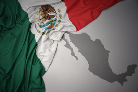 waving colorful national flag of mexico on a gray map background.