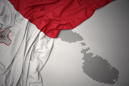 waving colorful national flag of malta on a gray map background. Фото со стока