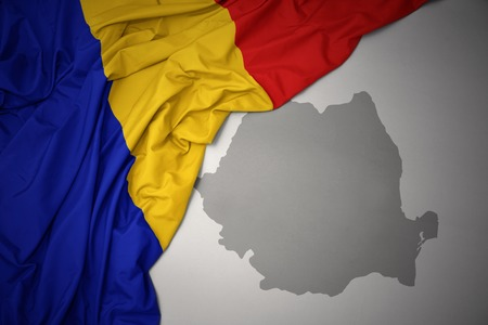 waving colorful national flag of romania on a gray map background.