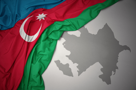 waving colorful national flag of azerbaijan on a gray map background. Фото со стока