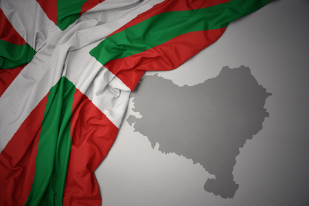 waving colorful national flag of basque country on a gray map background. Фото со стока
