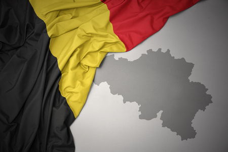 waving colorful national flag of belgium on a gray map background. Stock Photo