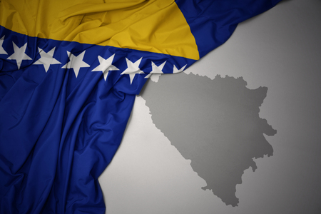 waving colorful national flag of bosnia and herzegovina on a gray map background.