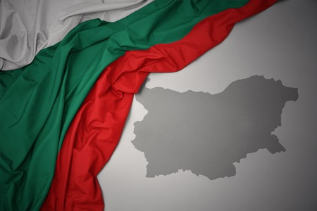 waving colorful national flag of bulgaria on a gray map background. Stock Photo