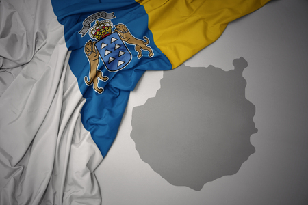 waving colorful national flag of canary islands and map of gran canaria on a gray map background.