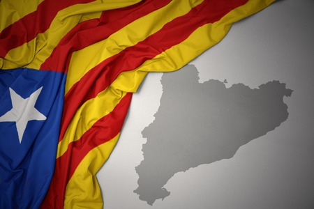 waving colorful national flag of catalonia on a gray map background.