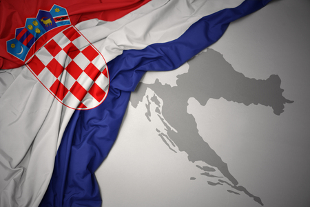 waving colorful national flag of croatia on a gray map background. Stock Photo