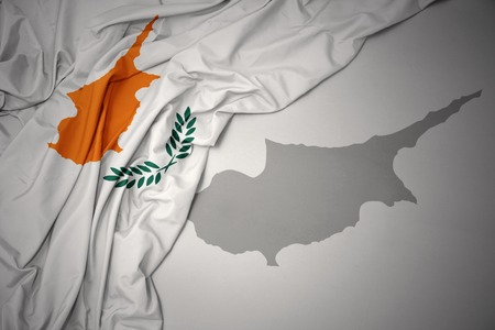 waving colorful national flag of cyprus on a gray map background. Stock Photo