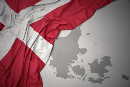 waving colorful national flag of denmark on a gray map background. Stock Photo
