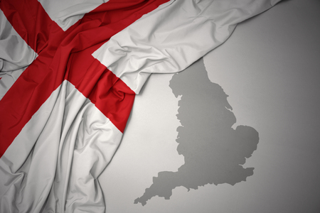 waving colorful national flag of england on a gray map background.