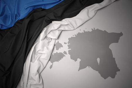 waving colorful national flag of estonia on a gray map background.