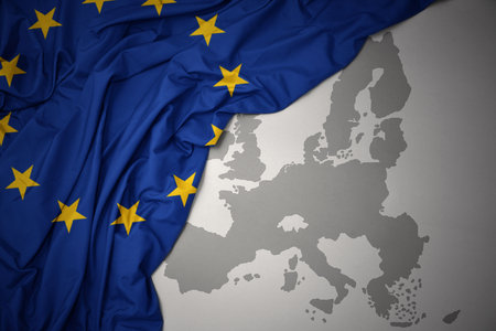 waving colorful national flag of european union on a gray map background.