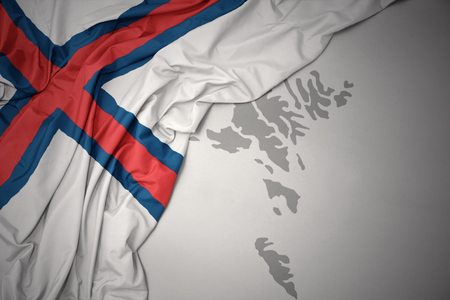 waving colorful national flag of faroe islands on a gray map background.