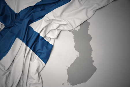 waving colorful national flag of finland on a gray map background.