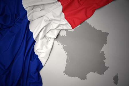 waving colorful national flag of france on a gray map background.