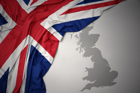 waving colorful national flag of great britain on a gray map background.