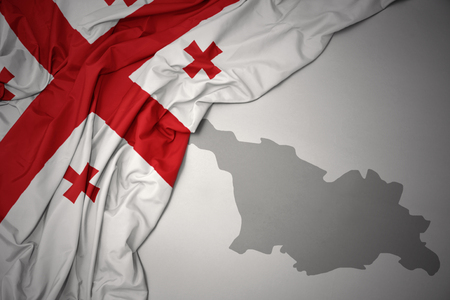 waving colorful national flag of georgia on a gray map background. Stock Photo