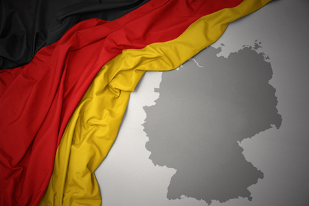 waving colorful national flag of germany on a gray map background.