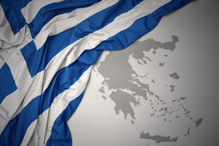 waving colorful national flag of greece on a gray map background.