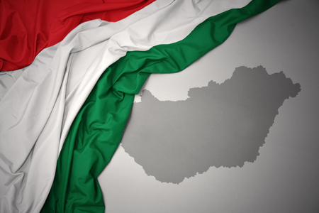 waving colorful national flag of hungary on a gray map background.