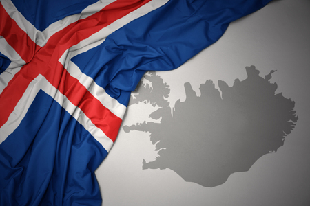 waving colorful national flag of iceland on a gray map background. Stock Photo