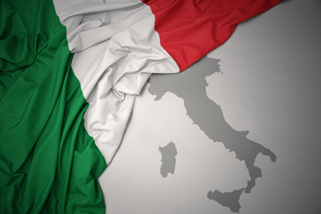 waving colorful national flag of italy on a gray map background.