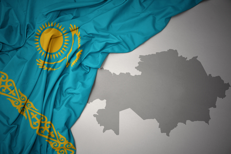 waving colorful national flag of kazakhstan on a gray map background. Stock Photo