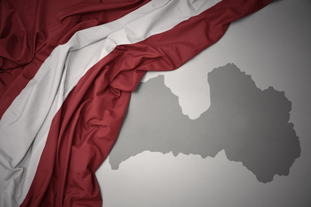 waving colorful national flag of latvia on a gray map background.