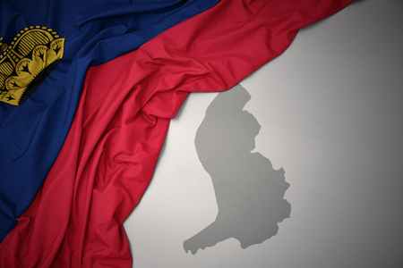 waving colorful national flag of liechtenstein on a gray map background. Stock Photo