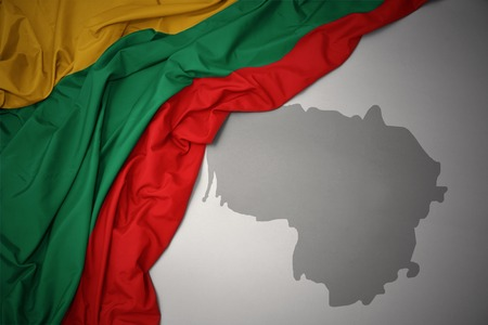 waving colorful national flag of lithuania on a gray map background. Stock Photo