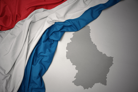 waving colorful national flag of luxembourg on a gray map background.