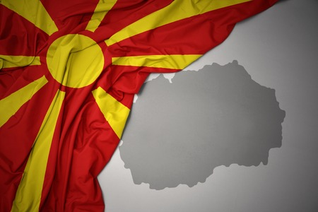 waving colorful national flag of macedonia on a gray map background.