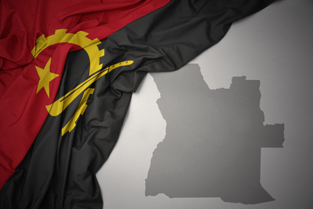 waving colorful national flag of angola on a gray map background. 3D illustration