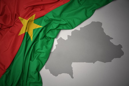 waving colorful national flag of burkina faso on a gray map background. 3D illustration