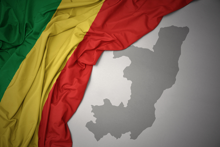 waving colorful national flag of republic of the congo on a gray map background. 3D illustration